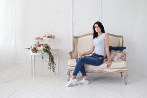 白い部屋で花とマカロンと一緒にいるソファの女性