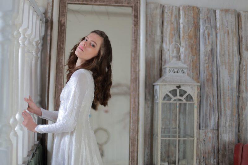 洋館のような部屋にいる白いドレスの女性