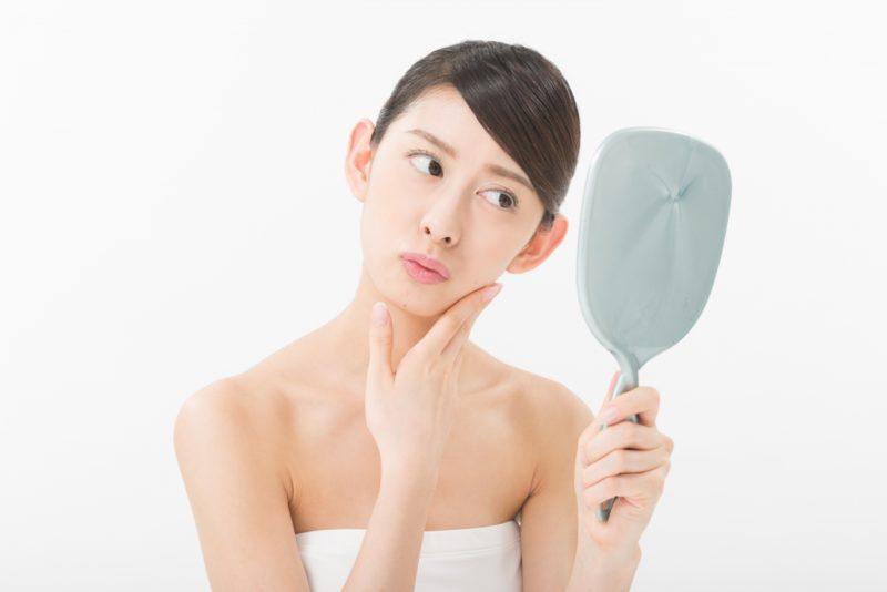 手鏡で肌を確認する女性