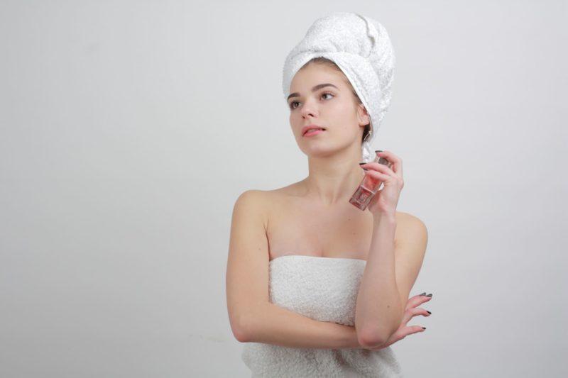 お風呂上がりに香水を付けようとしている女性