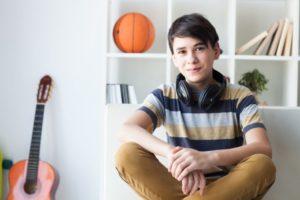 ソファに座って微笑んでいる外国人中学生