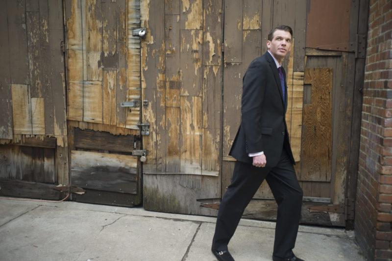 街中を歩いているスーツを着た外国人男性