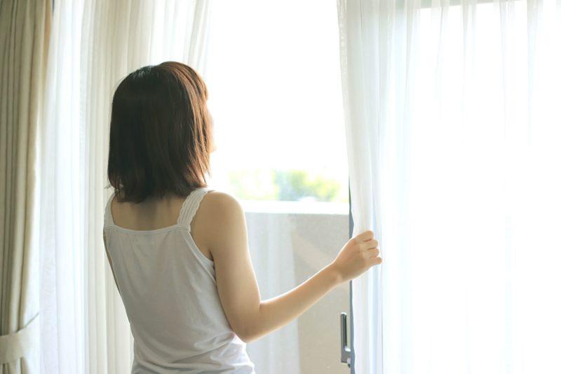 朝カーテンを開けて日光浴している女性