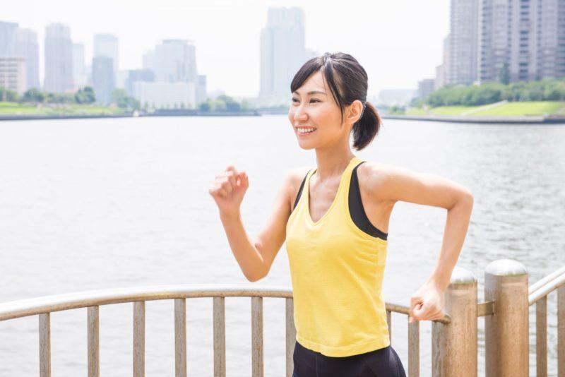 ビルが見える川沿いをジョギングしている女性
