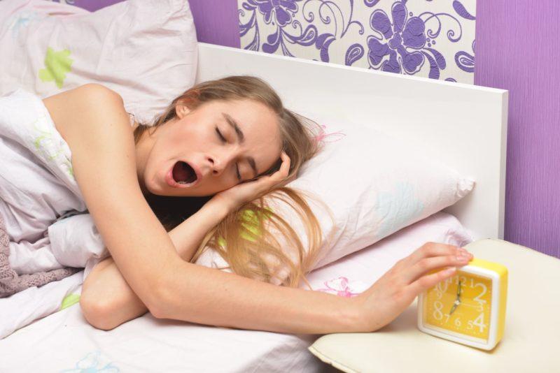 たくさん寝溜めしてやっと起きようとする女性