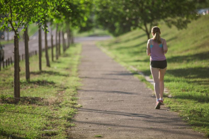 公園でジョギングをしている女性の後ろ姿
