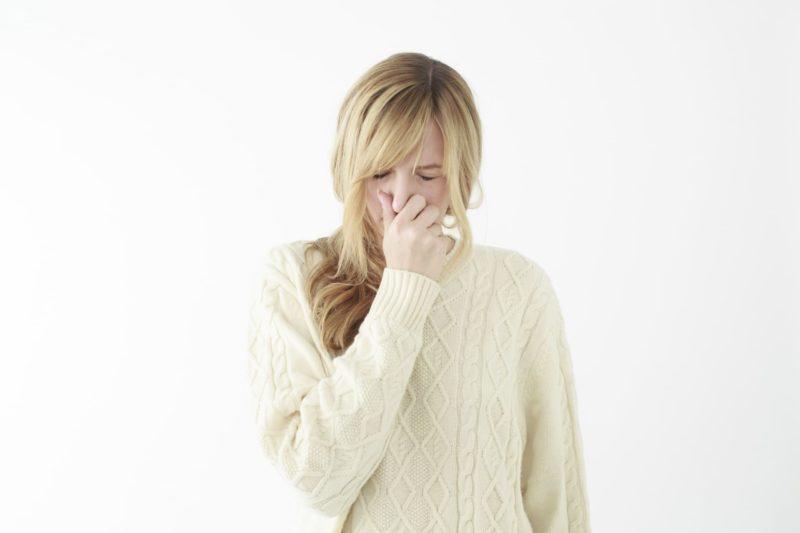 鼻を押さえている白ニットの女性