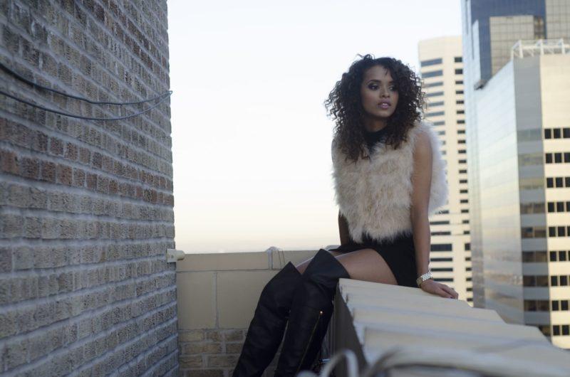 ベランダに座って外を見ているセクシーな黒人女性