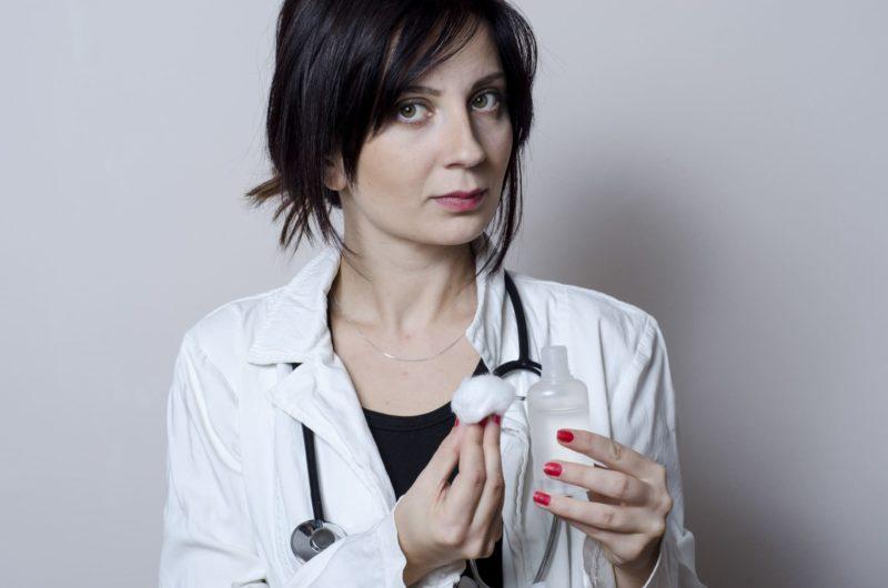 消毒薬をガーゼに付けようとしている鋭い目線の女医さん