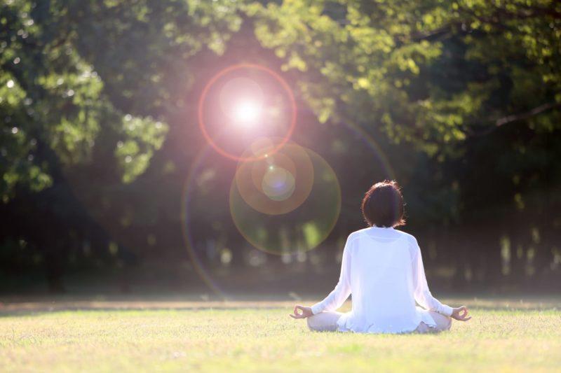 日光浴をしながらヨガをする白い服の女性の後ろ姿