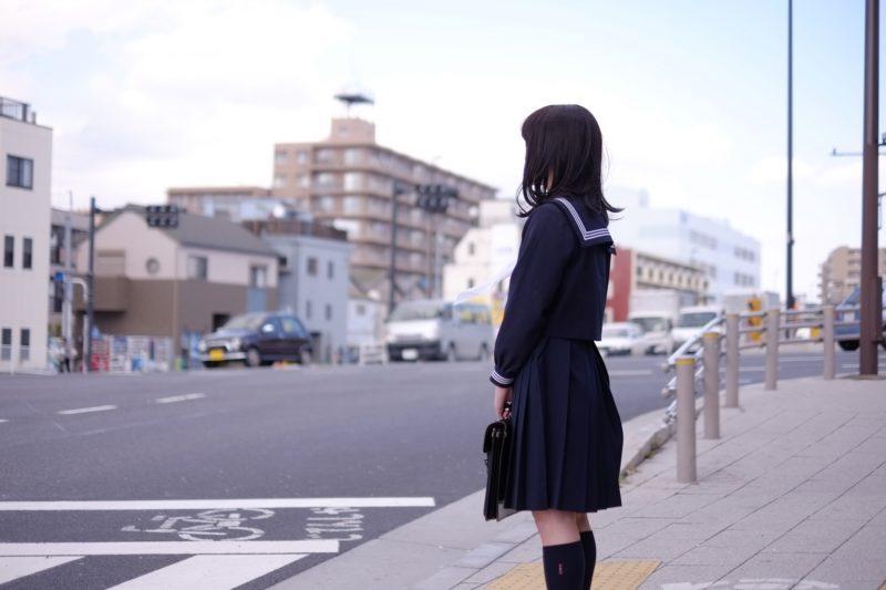 横断歩道の前に立つ女子高生