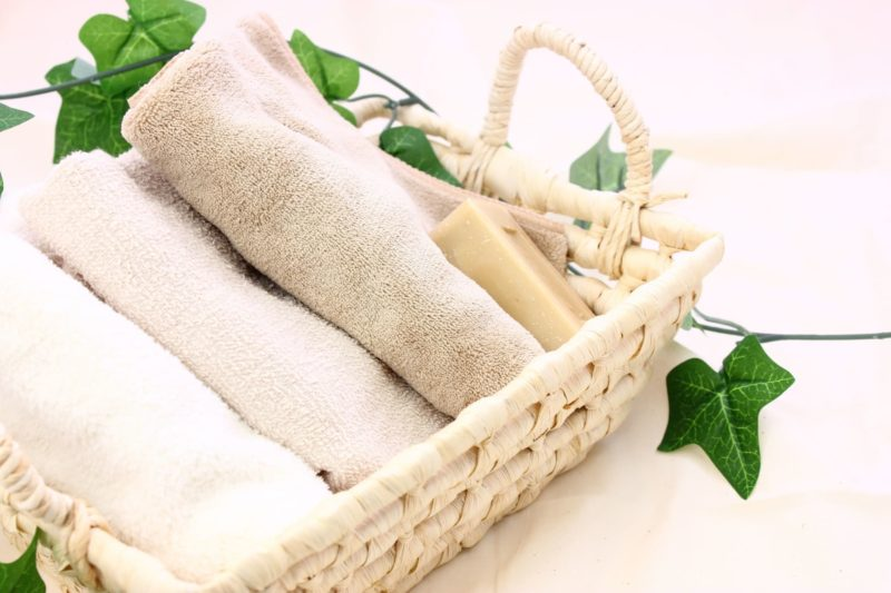 清潔感のある空間に、ナチュラルウッドの木製のトレーがあり、その上に丸められたタオル3枚と石鹸1つが置かれている