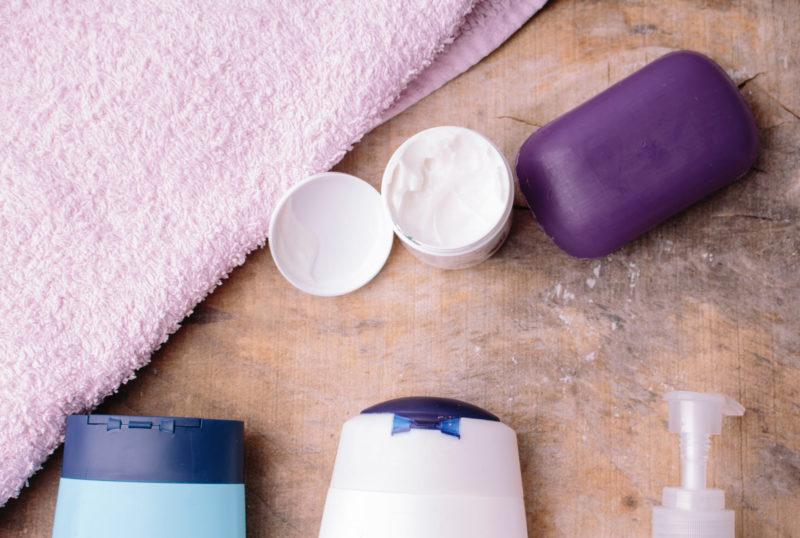 白みがかった木製のテーブルの上に、薄紫色のタオルと紫色の石鹸、その他に4種類のスキンケアグッズが置かれている