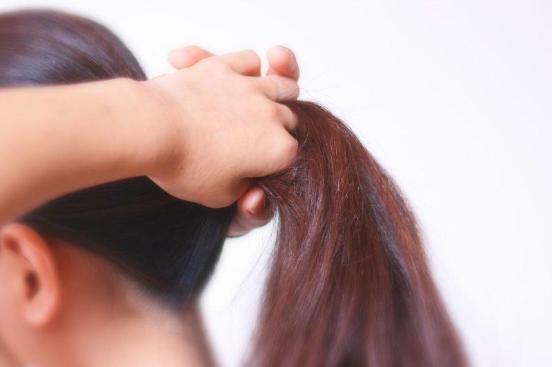 後ろ髪を束ねようとしている女性