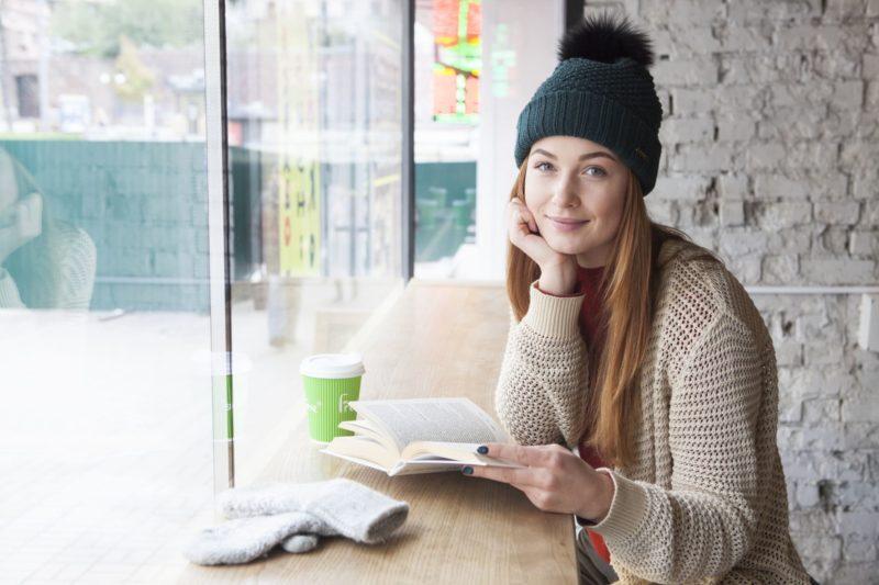 カフェで本を読みながら右手で頬杖をついている女性