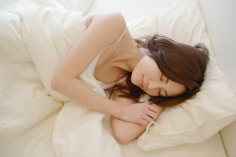白い枕とシーツで横向きで寝る女性