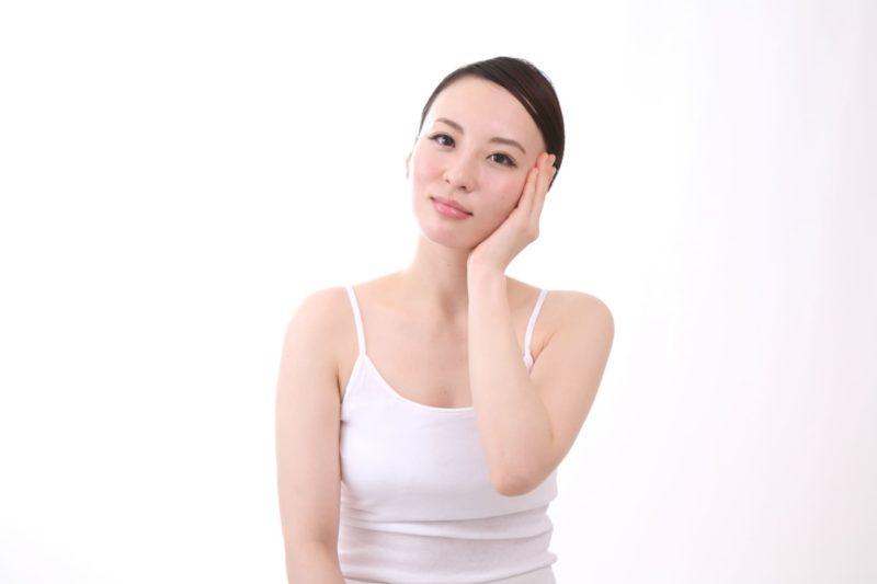 白いタンクトップを着た女性が左頬に左手で触れている