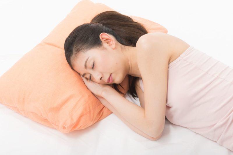 オレンジ色の枕に両手を頬の下に添え横向きで寝るポニーテールの女性