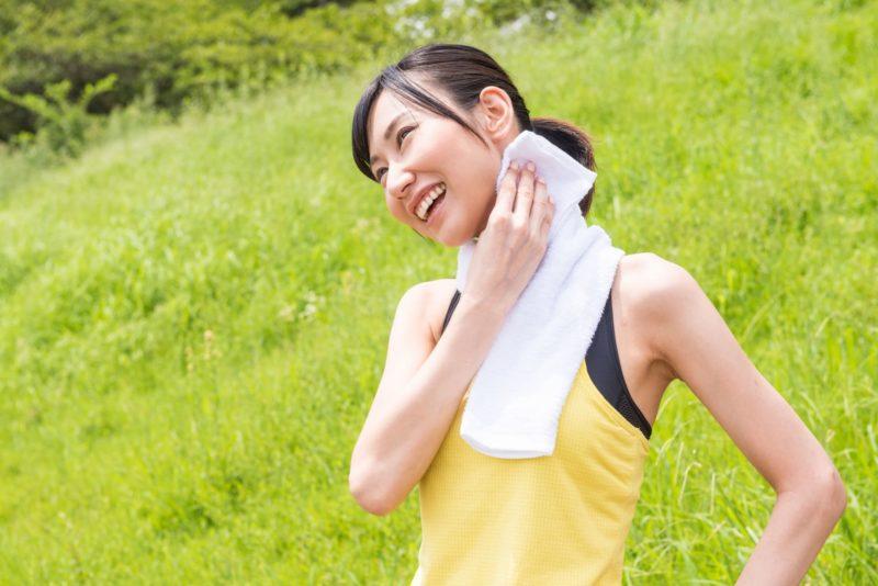 汗をふいて微笑む女性