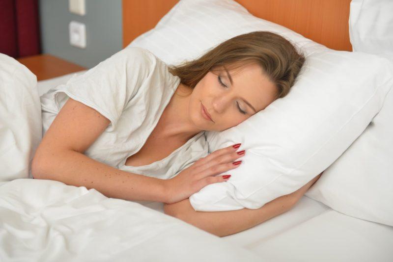 清潔そうなベッドで眠る女性