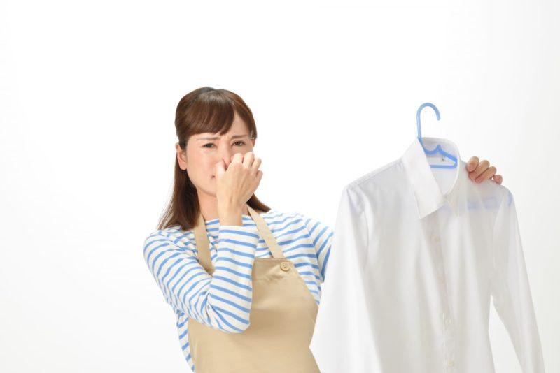 洗濯ものを持ち鼻をつまむ女性