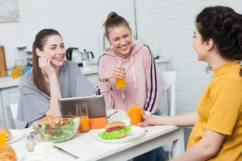 ルームメイトと一緒に楽しく食事をしている写真