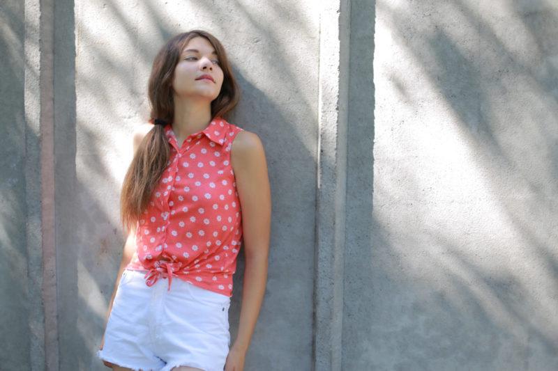 顔を上向き加減で立っているピンクの水玉を着ている女性