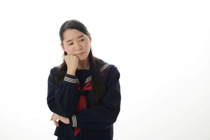 頬杖をして考え込んでいる女子中学生