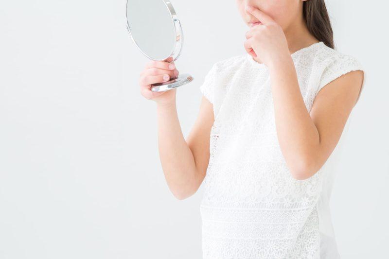 鏡を見ながら鼻を触っている女の子