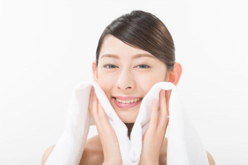 洗顔して優しくタオルで顔を拭いている女性
