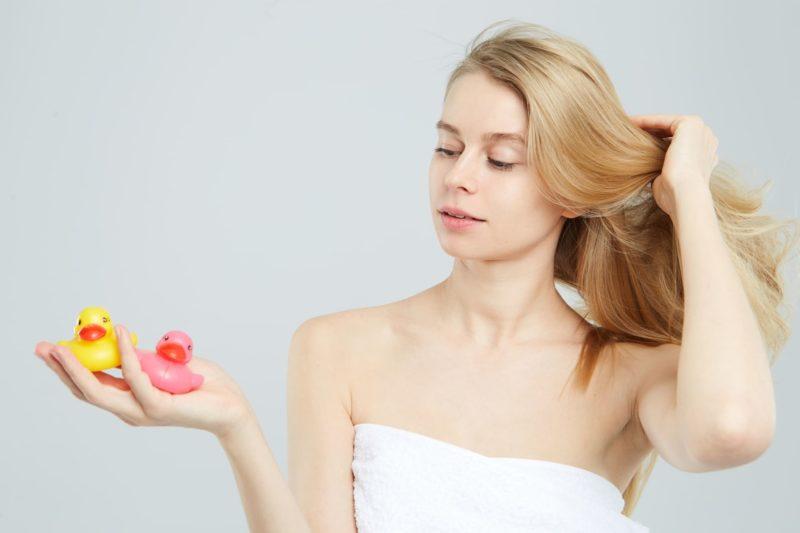 アヒルのおもちゃを2つ手に取り、髪をなびかせているバスタオルの女性