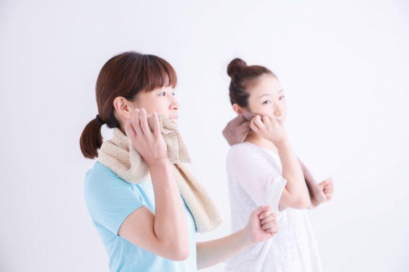女性二人が運動した後汗を拭いている写真