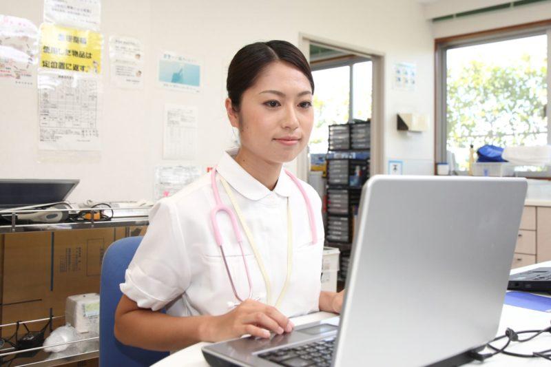 パソコンを使って処方箋や診療報酬を計算している事務員
