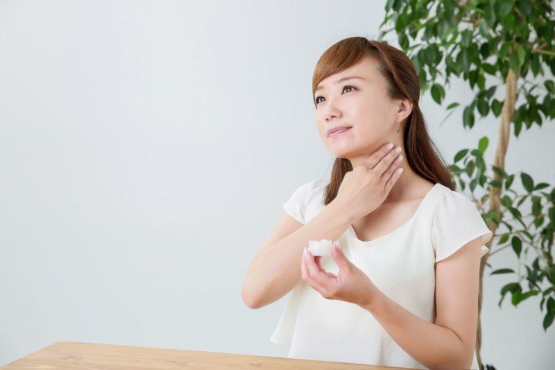 首に丁寧に保湿クリームを塗っている日本人女性
