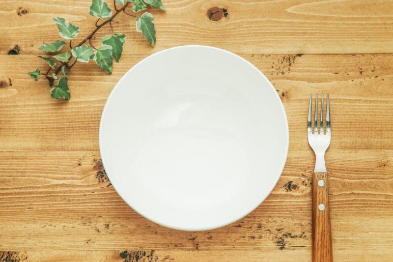 木目調のテーブルに置かれている皿とフォーク