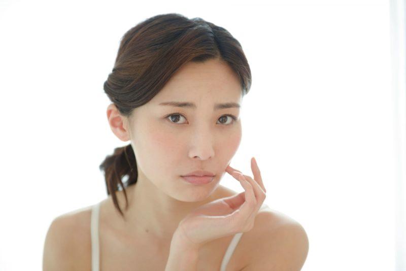 自分の顔や肌に不満を持っている表情をしている女性