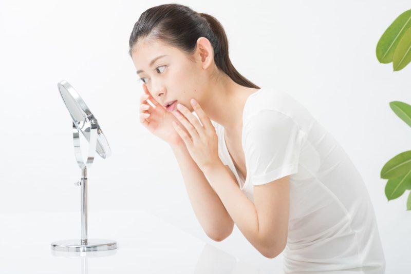 顔をのぞきこんで鏡で一生懸命確認をしている女性