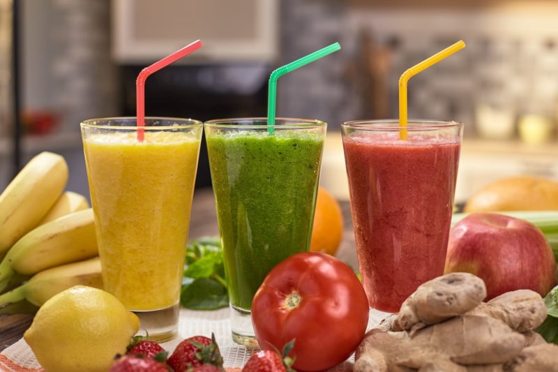 左からイエロー・グリーン・レッドのフルーツ & 野菜ジュースが透明のグラスにたっぷりと入っている。その周りにはバナナやトマトなどの野菜とフルーツがちりばめられている。