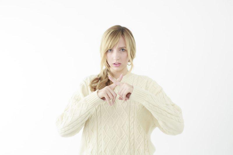 白いニットを着たブロンドの白人女性が両手の人差し指で「×(バツ)」を作っている