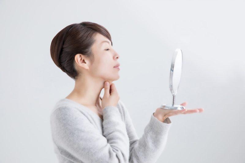 首元を押さえ鏡を手の平に乗せてる女性