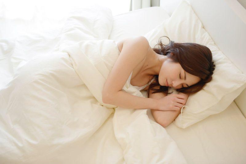 白いベッドで気持ちよさそうに眠っている女性