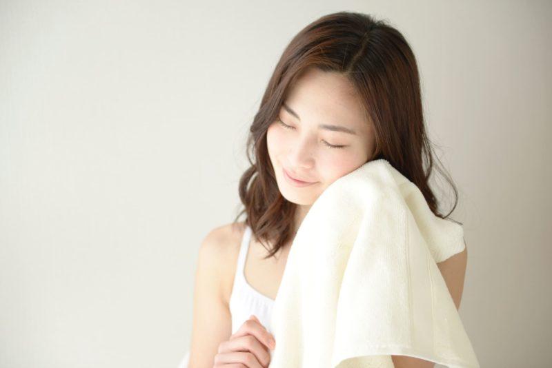 白いタオルで頬を拭いている女性