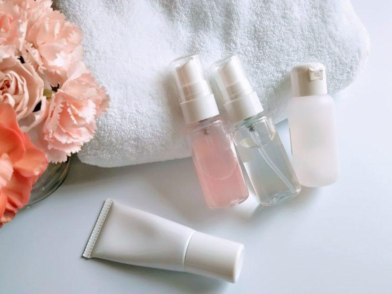 化粧品4つとタオルと花