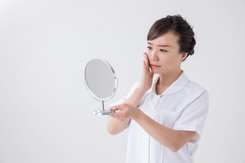 手鏡を手に持ち、神妙な面持ちで眉をひそめている白衣を着た女性
