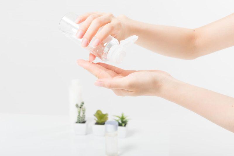 透明のボトルに入っている化粧水を手の平に垂らそうとしている