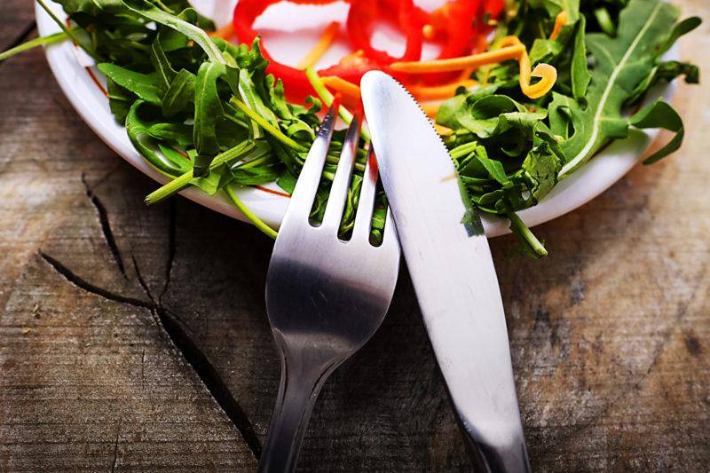お皿にサラダが盛り付けられている。フォークとスプーンが添えられている。