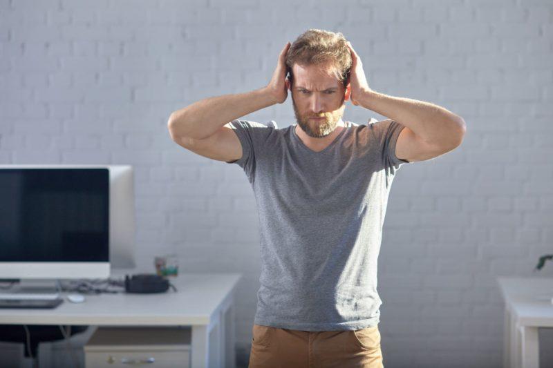どうしようもなく頭を抱えるグレーTシャツの白人男性