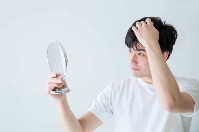 鏡で頭皮を気にする男性