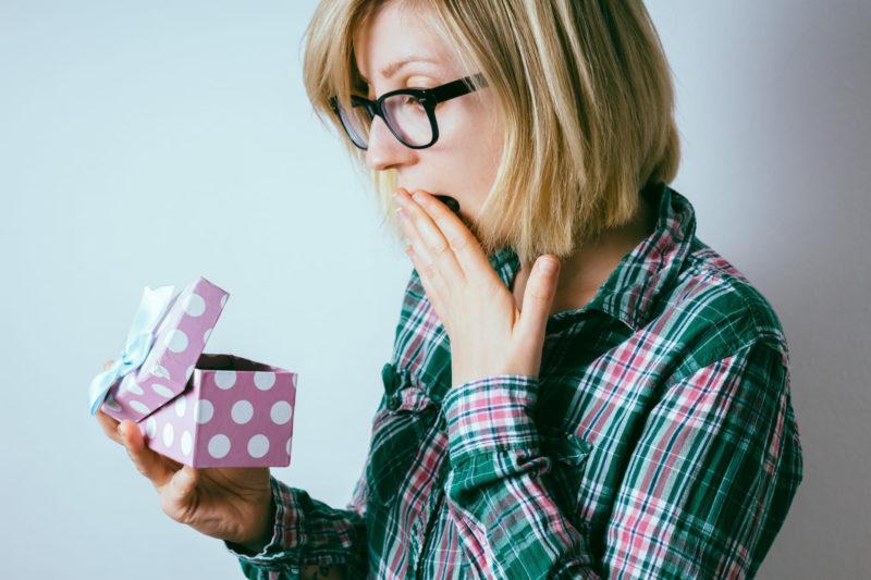 紫のボックスを開けて中身にびっくりしている女性