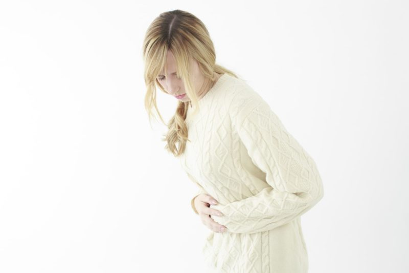 胃や腸の具合が悪く腹を押さえている女性